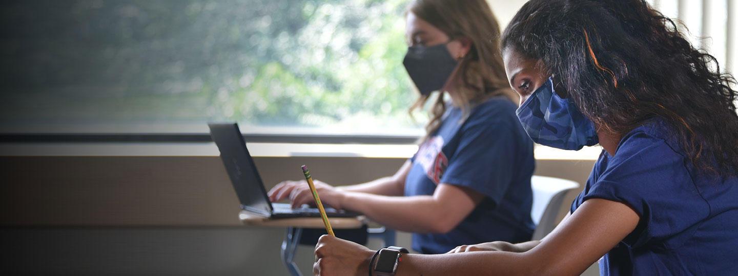 Photo of two female students in a classroom wearing masks.