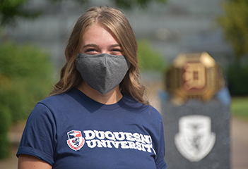 Female student wearing mask on campus.