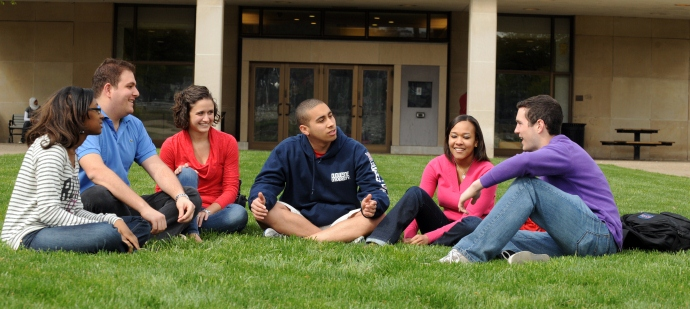 six students sitting on the grass on campus talking