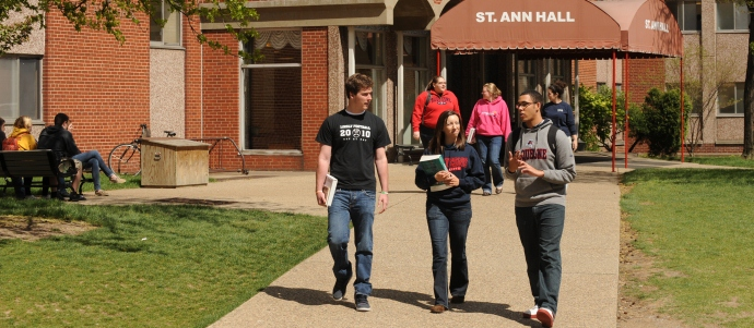 Three students walking out of a residence hall on campus
