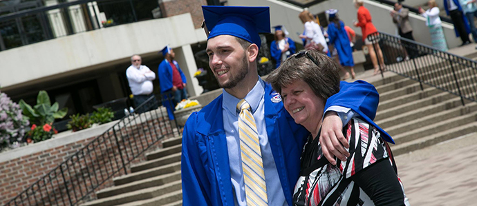 Student standing with mother at graduation