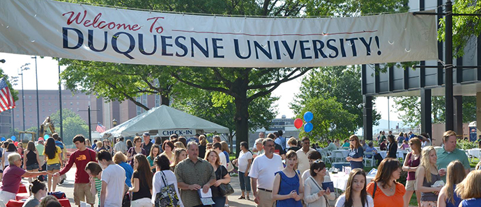 Welcome to Duquesne University Banner Hanging over Academic Walk with people walking underneath