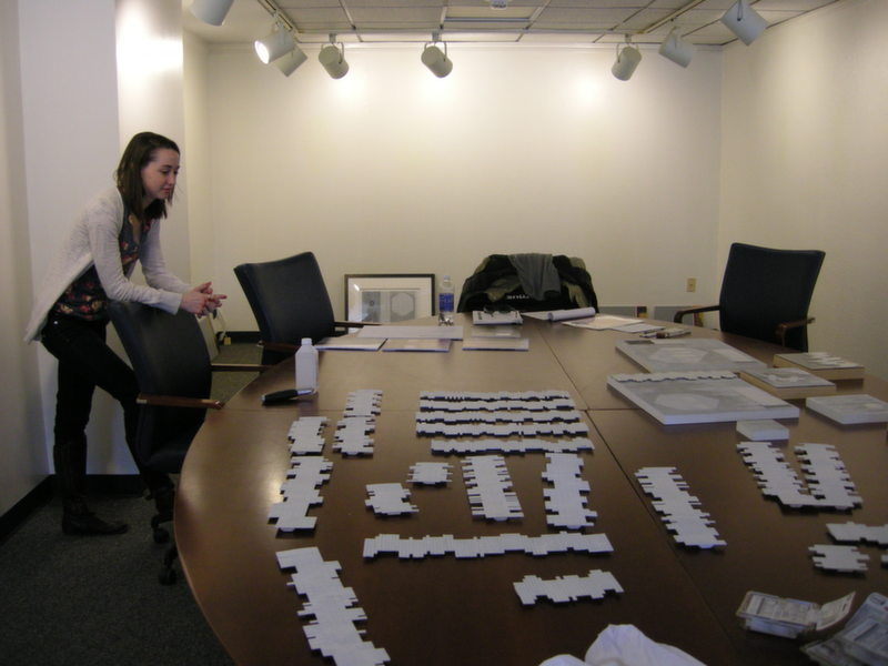 Student Assistant Curator Hannah Sanders looks over some of the pieces prior to the exhibit installation process.