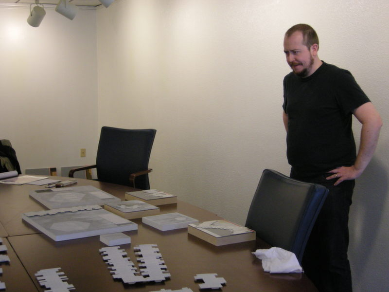 Artist Andrew Hairstans surveys his pieces as he prepares for the exhibit installation.