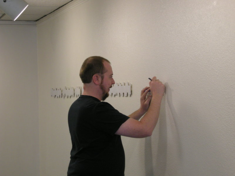 Artist Andrew Hairstans begins the installation process.