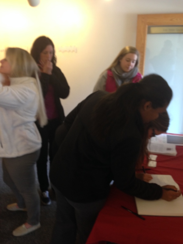 Students from Dr. Julia Sienkewicz's Fides Learning Community class (ARHY 217C, Religion, Reason, and Visual Culture) sign the exhibit guest book.