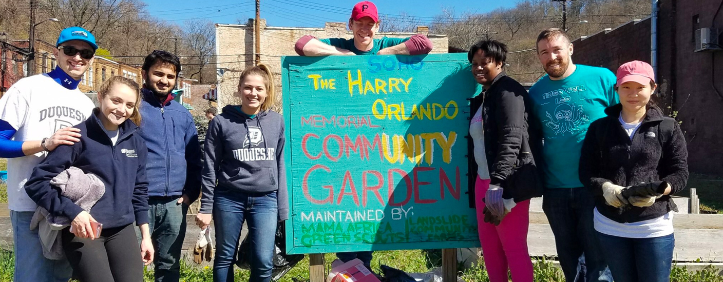 student volunteers posing next to community garden sign