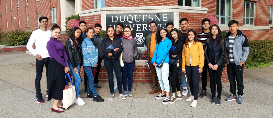 international students on campus in front of Duquesne sign
