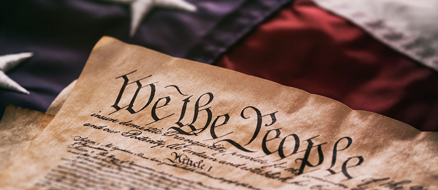 We The People written on the Constitution and an American Flag