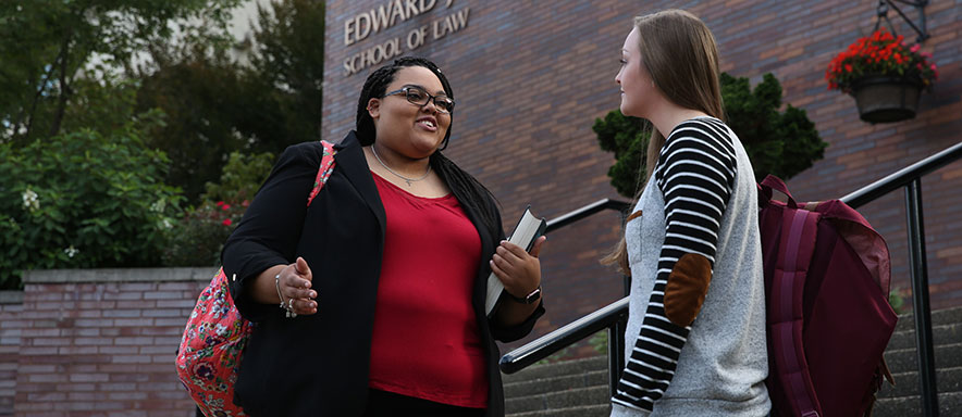 Two females talking in front of the law school