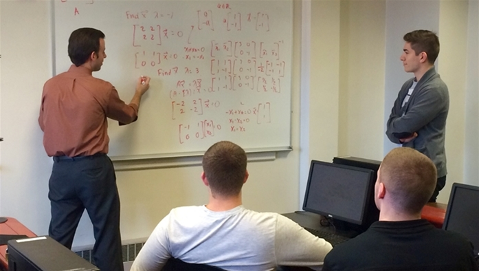 Professor Tierney reviews math problems with students