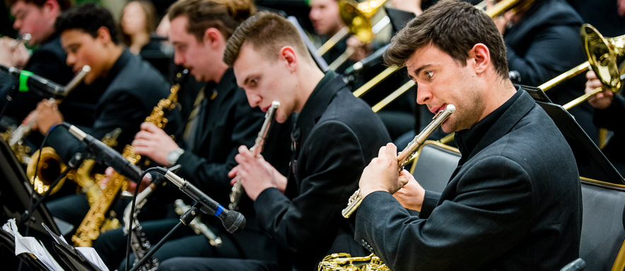 Saxophone students doubling on flutes at a jazz band concert