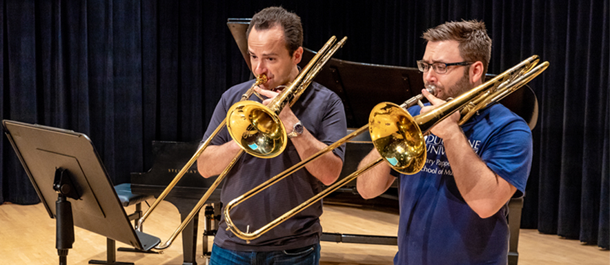 Trombone student and teacher playing together