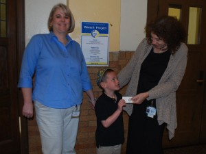 Dr. Kara McGoey, left, and Avi Munro flank a student with a mensch card.