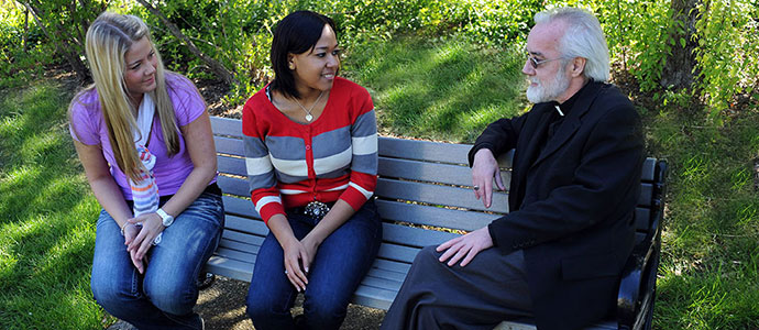 Photo of Fr. French and two students sitting on a bench