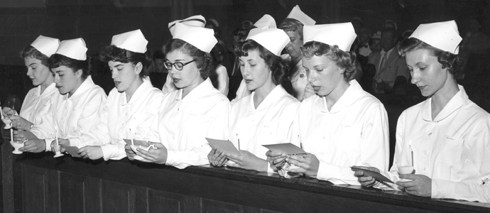 Black and white photo of nurses in uniforms in church pew circa 1957