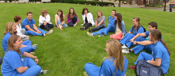 Photo of students in scrubs having class outdoors