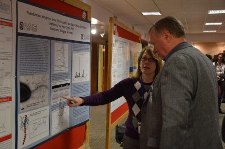 A graduate student explains her poster to Dr. Alan Seadler, Associate Academic V.P. for Research.