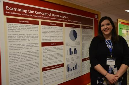 Anna Blake, a graduate student in the School of Education, stand next to her poster,