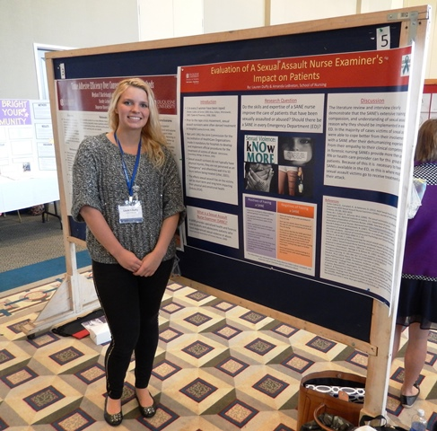"Lauren Duffy from the School of Nursing poses by her poster, ""Evaluation of A Sexual Assault Nurse Examiner's Impact on Patients."""