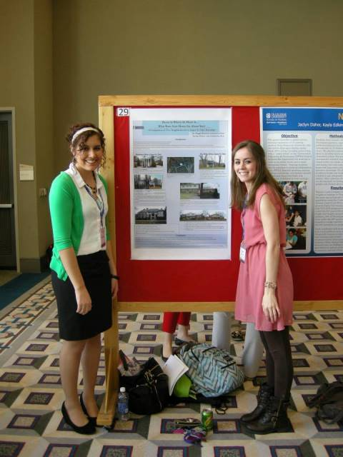 Justine Huber and Maggie Betschart, students in the McAnulty College and Graduate School or Liberal Arts. pose next to their poster.