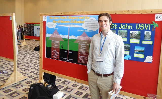 "Freshman Michael Lawrence stands next to his poster, ""The Cave: Plato's Allegory and the Rise of Western Civilization."""