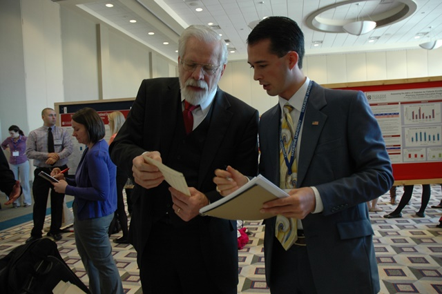 Business student Jordan Oeler gets input from investment manager Ronald H. Muhlenkamp.