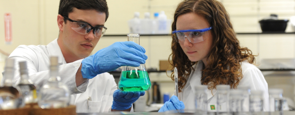 Students in labcoats looking at a beaker with green liquid.