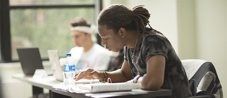 Secondary ed student in class studying in class with another student in background studying