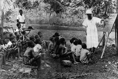 Oubangui, 1928. Fr. Adrien Leperdriel teaching under a tree.