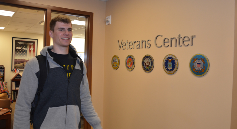 Male student walking into Veterans Center on campus