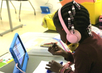 Child with Tablet Participating in Virtual Learning from Writing Center