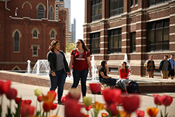 Photo of students walking by fountain on academic walk.