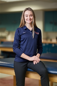 Athletic training student sitting on table