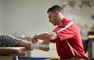 Male athletic training student taping an ankle