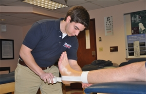 Athletic training student practicing ankle taping
