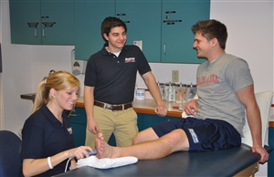Athletic training student providing ultrasound treatment to ankle -- additional student part of conversation