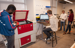 Students working around a laser engraver in Bob's Launch Pad, a maker space.