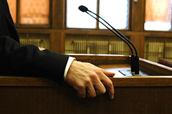 Close-up of the arm of a person wearing a suit and standing at a podium