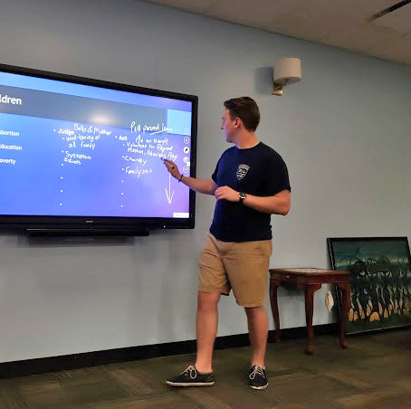 student giving presentation on television screen