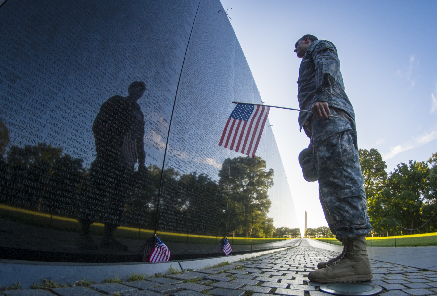 Image of soldier standing in front of Vietnam Memorial in Washington D.C.