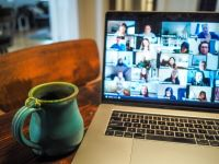 Zoom attendees on laptop screen with coffee mug