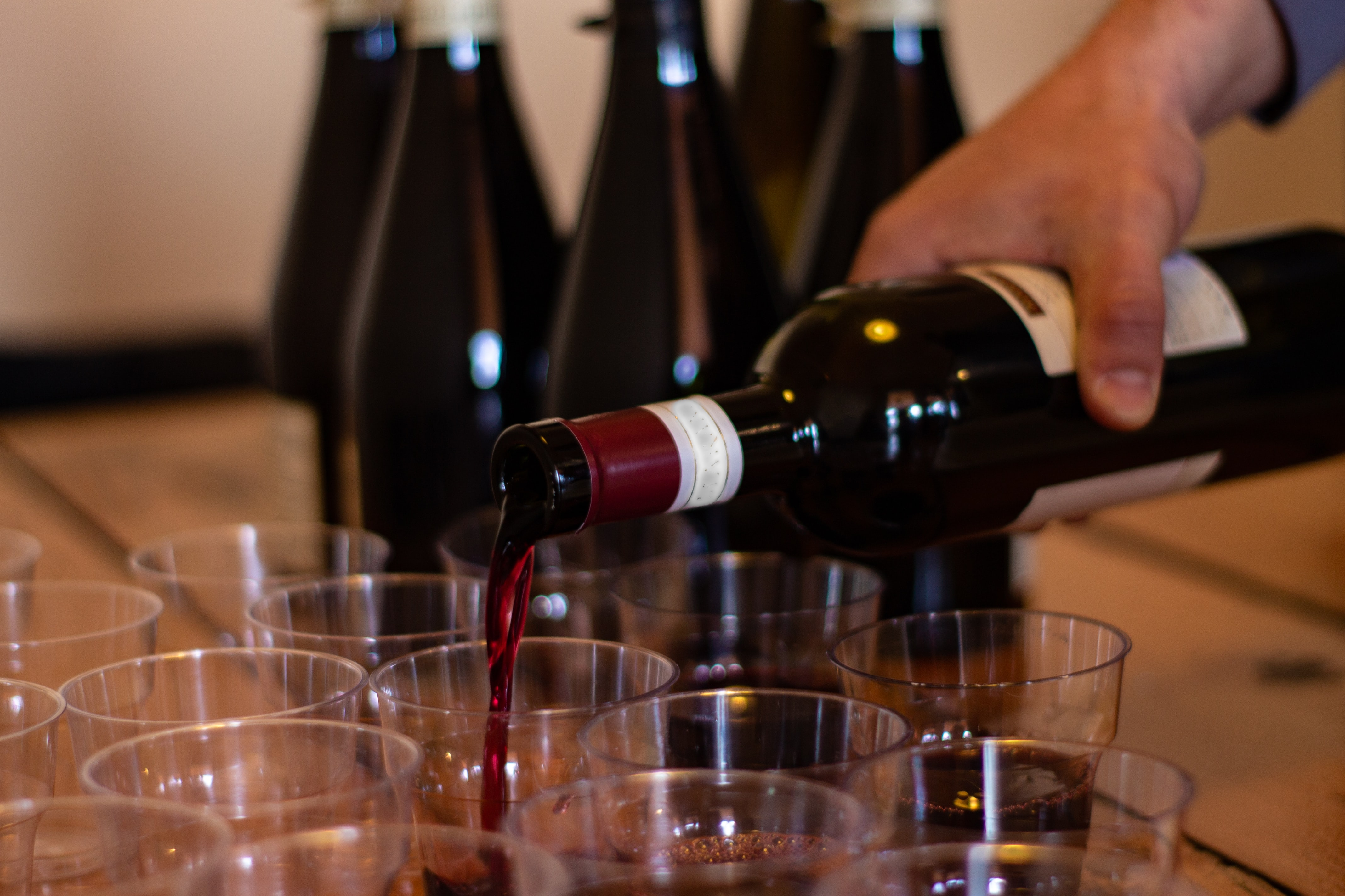 photo of red wine being poured into glasses