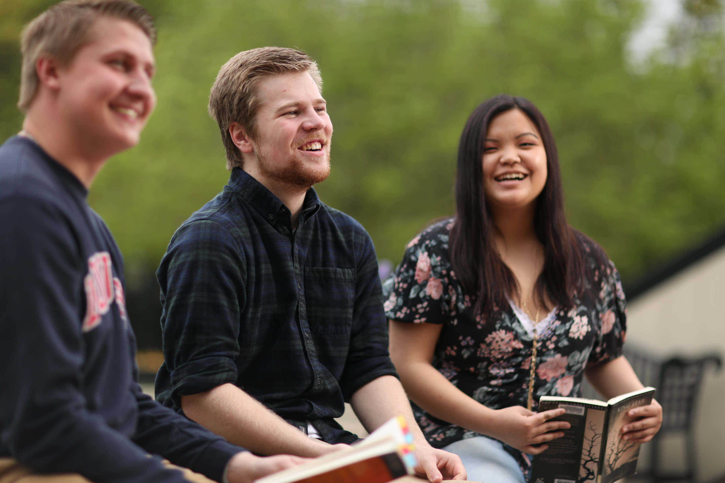 photo of three students laughing together while sitting near a fountain