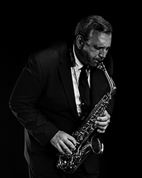 Mike Tomaro playing an alto saxophone