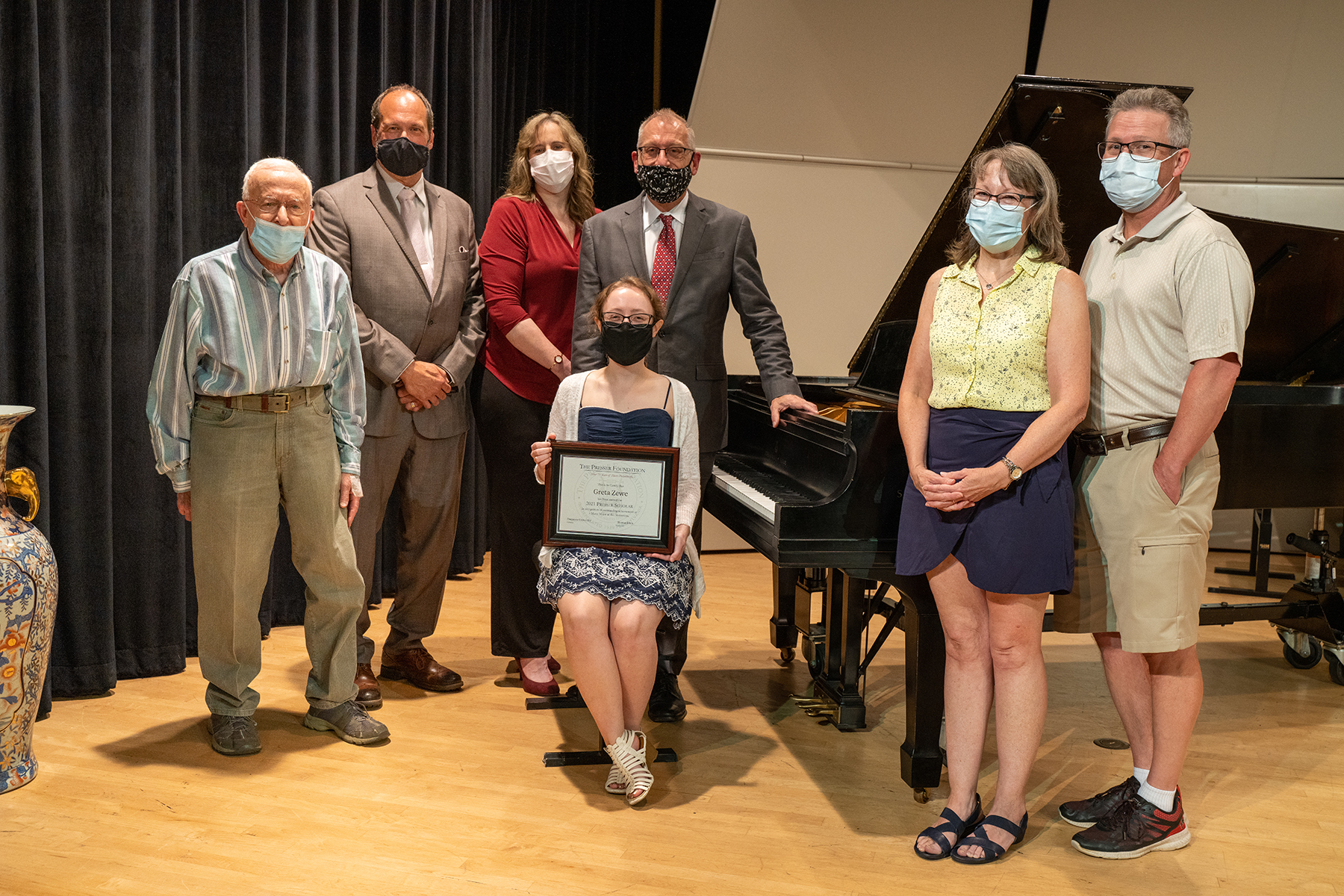 Greta Zewe poses in front of a piano with faculty mentors and her parents.