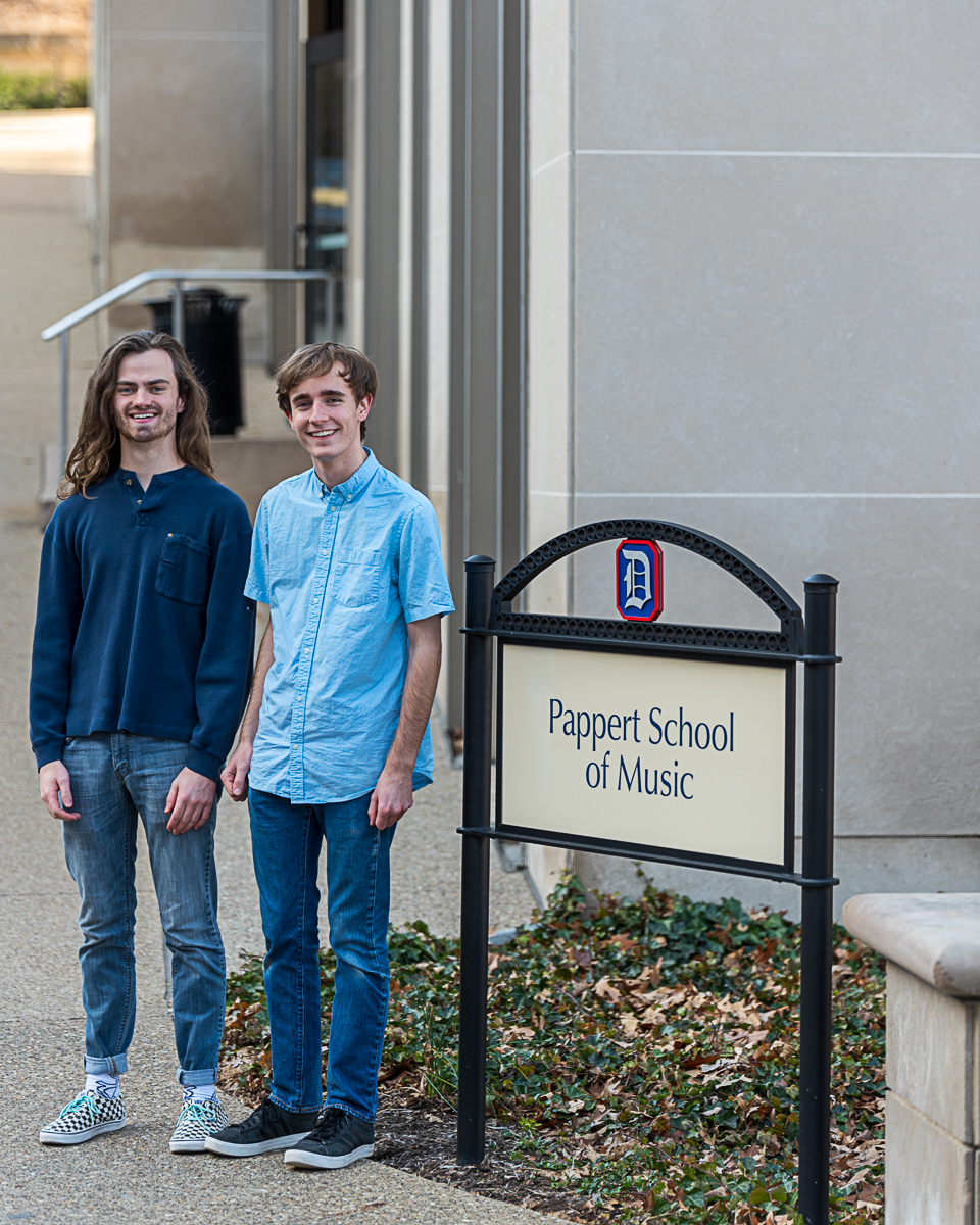 Spencer McNeill and Alex Weibel stand next to Mary Pappert School of Music