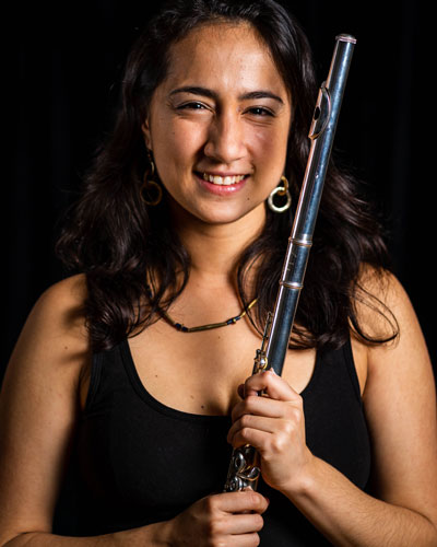 Marie Hincapie holds a flute in front of a black background