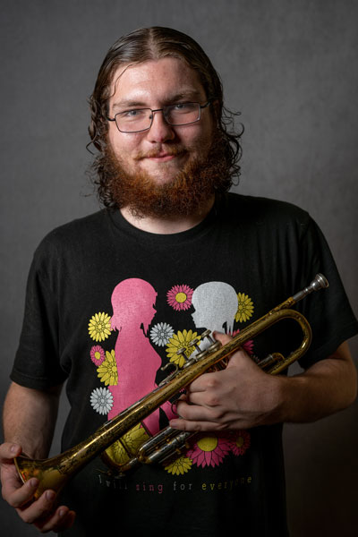 Thomas Houghton holds a trumpet in front of a gray backdrop.