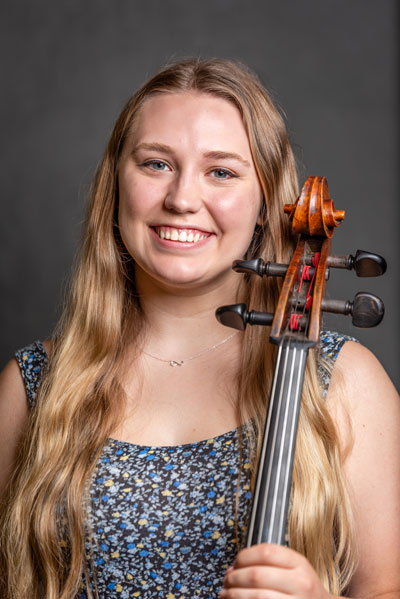 Olivia Burik holds a cello and stands in front of a gray background